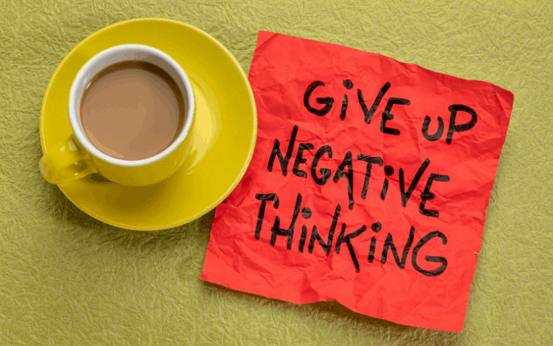 Napkin that has Give up negative thinking wrote on it laying by coffee cup