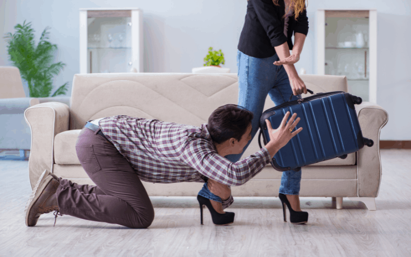 Women leaving with suitcase and man on floor begging woman to stay